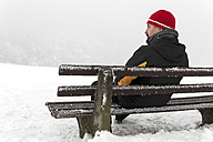 Germany, Baden-Wuerttemberg, Waldshut-Tiengen, man on icy bench - MIDF000039