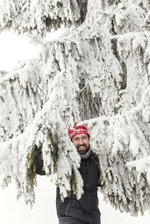 Germany, Baden-Wuerttemberg, Waldshut-Tiengen, smiling man in snow-capped fir tree - MIDF000040