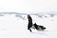Germany, Baden-Wuerttemberg, Waldshut-Tiengen, woman and dog running in snow - MIDF000055