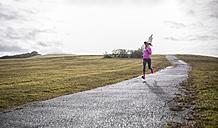 Spain, Gijon, sportive young woman running on path - MGOF000080