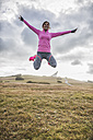 Spain, Gijon, sportive young woman jumping on meadow - MGOF000102