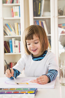 Portrait of smiling little girl painting with watercolours - LVF002810