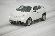 Germany, white car driving on snow-covered country road - CHP000058