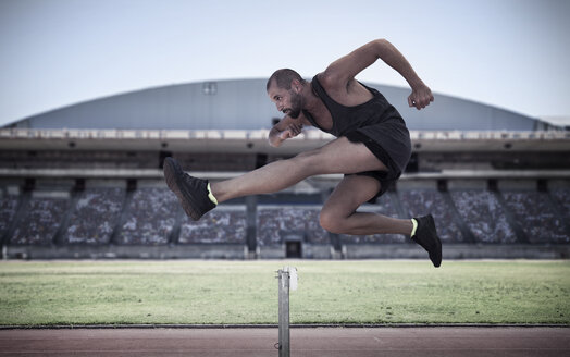 Athlete jumping over hurdle - ZEF007477