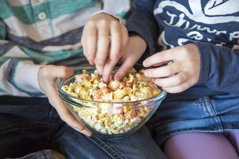 Hands of boy and girl taking coloured popcorn - SARF001363