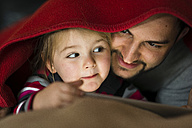 Father and daughter with digital tablet under blanket - UUF003360
