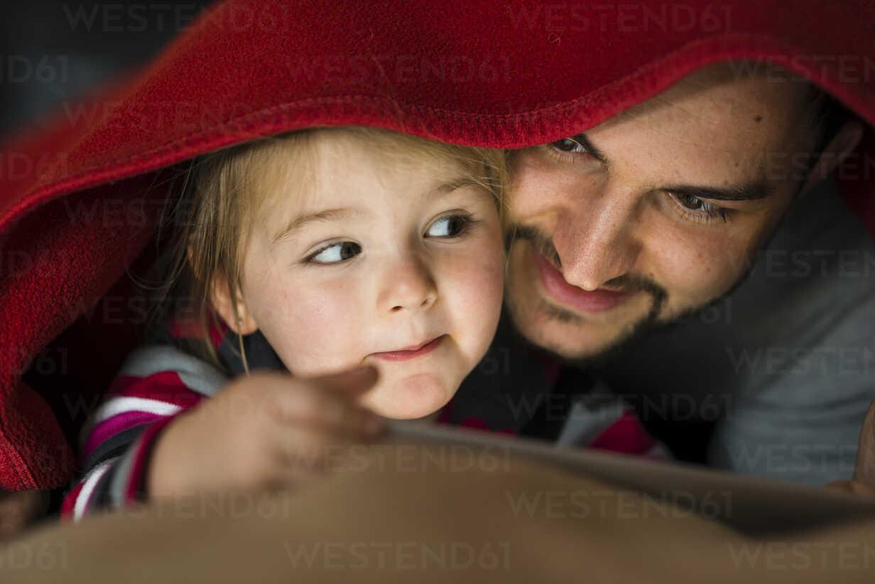 Father and daughter with digital tablet under blanket - UUF003360 - Uwe Umstätter/Westend61