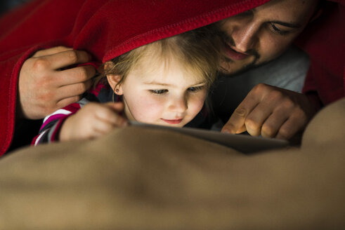Father and daughter with digital tablet under blanket - UUF003361