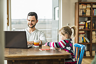 Father and daughter with laptop and game at wooden table - UUF003363