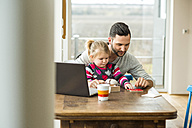 Father and daughter with laptop and game at wooden table - UUF003364