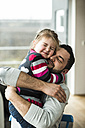 Father and daughter hugging at home - UUF003366
