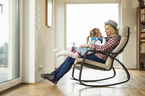 Mother and daughter on rocking chair with headphones - UUF003380