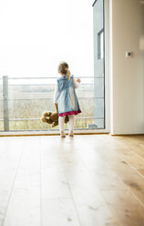 Girl holding teddy looking out of window - UUF003385