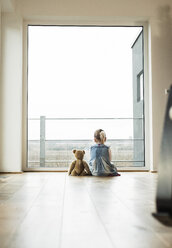 Girl sitting next to teddy looking out of window - UUF003387