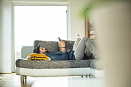 Man lying on sofa using digital tablet - UUF003388