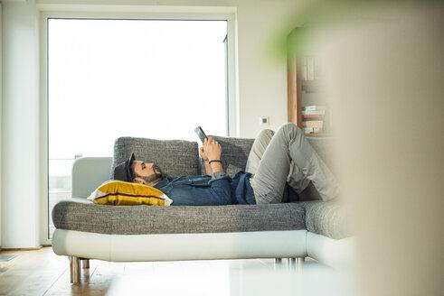 Man lying on sofa using digital tablet - UUF003388