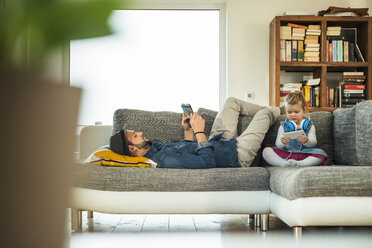 Father and daughter with digital tablet and smartphone on sofa - UUF003389