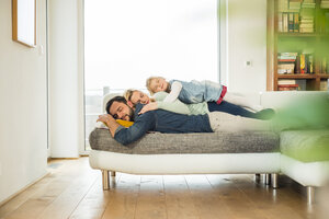 Family lying on couch on top of each other with closed eyes - UUF003392