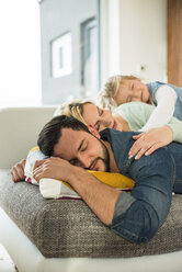 Family lying on couch on top of each other with closed eyes - UUF003402