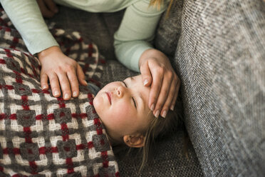 Mother touching forehead of ill daughter lying on couch - UUF003393