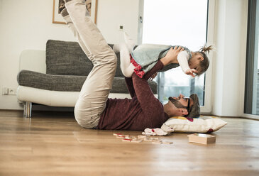Happy father and daughter playing at home - UUF003404