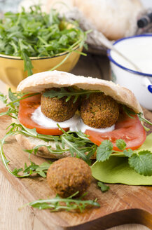 Homemade falafel, tomato, yoghurt sauce, rocket and mint in pita bread on chopping board - ODF001123