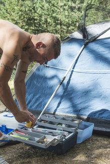Bulgaria, man preparing hook for fishing - DEGF000212