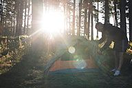 Bulgaria, man fixing tent in the forest - DEGF000222