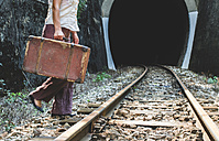 Bulgaria, Woman on railway road and tunnel, suitcase in hand - DEGF000289