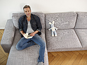 Mature man sitting on sofa, holding book - RHF000502