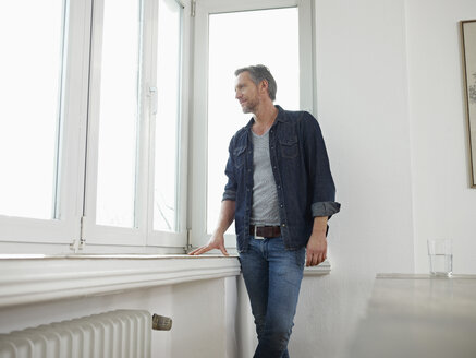 Germany, Cologne, Mature man standing at window, looking out - RHF000516