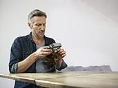 Mature man sitting at table with old camera - RHF000517