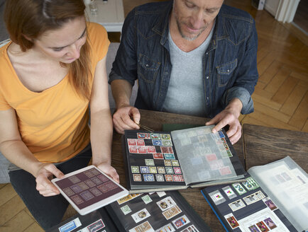 Mature man and young woman looking through stamp collection - RH000525