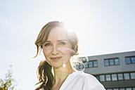 Portrait of smiling businesswoman at backlight - PDF000773