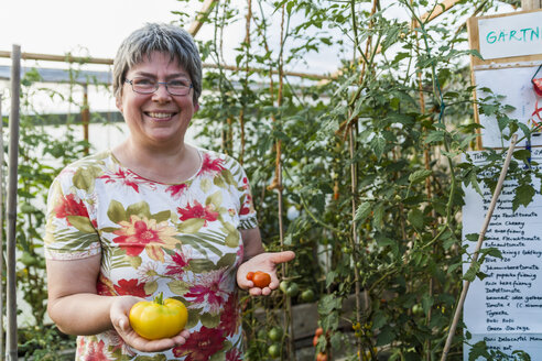 Woman in greenhouse holding red and yellow tomato - TCF004571