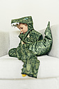 Little boy wearing dinosaur costume sitting on the couch - MFF001481