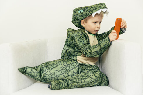 Little boy wearing dinosaur costume sitting on the couch with smartphone - MFF001483