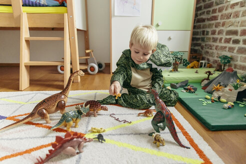 Little boy wearing dinosaur costume playing with toy dinosaurs - MFF001488