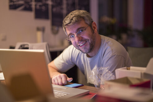 Smiling man with laptop and smartphone at desk - SHKF000250