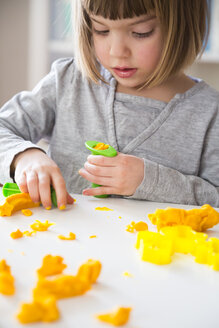 Little girl playing with yellow modeling clay - LVF002868