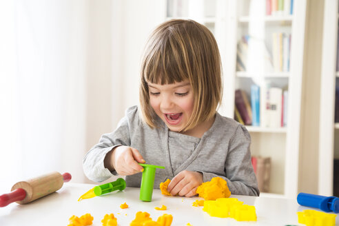 Little girl playing with yellow modeling clay - LVF002867