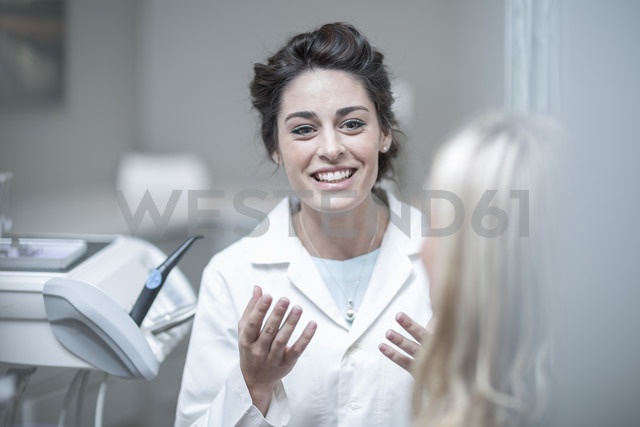 Dentist explaining procedure to patient sitting in dentist's chair - ZEF003811