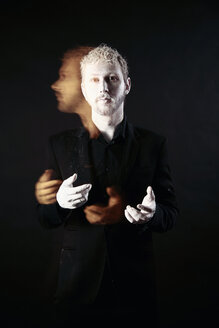 Man with white hands and white face in front of black background, long exposure - VE000032