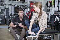 Young woman buying bicycle shoes, salesman advising - ZEF005037