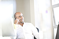 Portrait of businessman telephoning with smartphone at desk in an office - ZEF003533