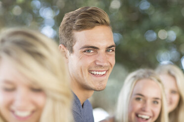 Smiling young man among frinds outdoors - ZEF004615