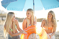 Three happy young women under beach umbrella - ZEF004624