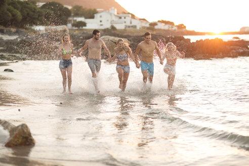 Five friends running on a beach in waves - ZEF004634