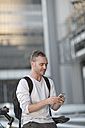Blond man on bicycle using smart phone - ZEF004505