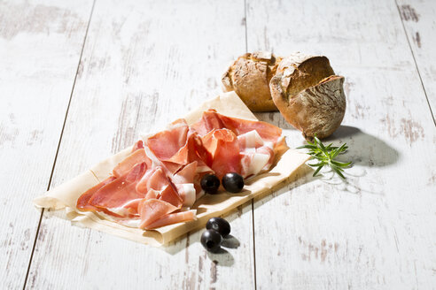 Parma ham on greaseproof paper, rolls and black olives on bright wood - MAEF009791